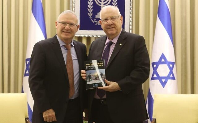 The head of Tel Aviv's Institute for National Security Studies think tank Amos Yadlin, left, presents President Reuven Rivlin with the organization's strategic assessment for 2020 at the President's Residence on January 6, 2020. (Chen Galili/INSS)