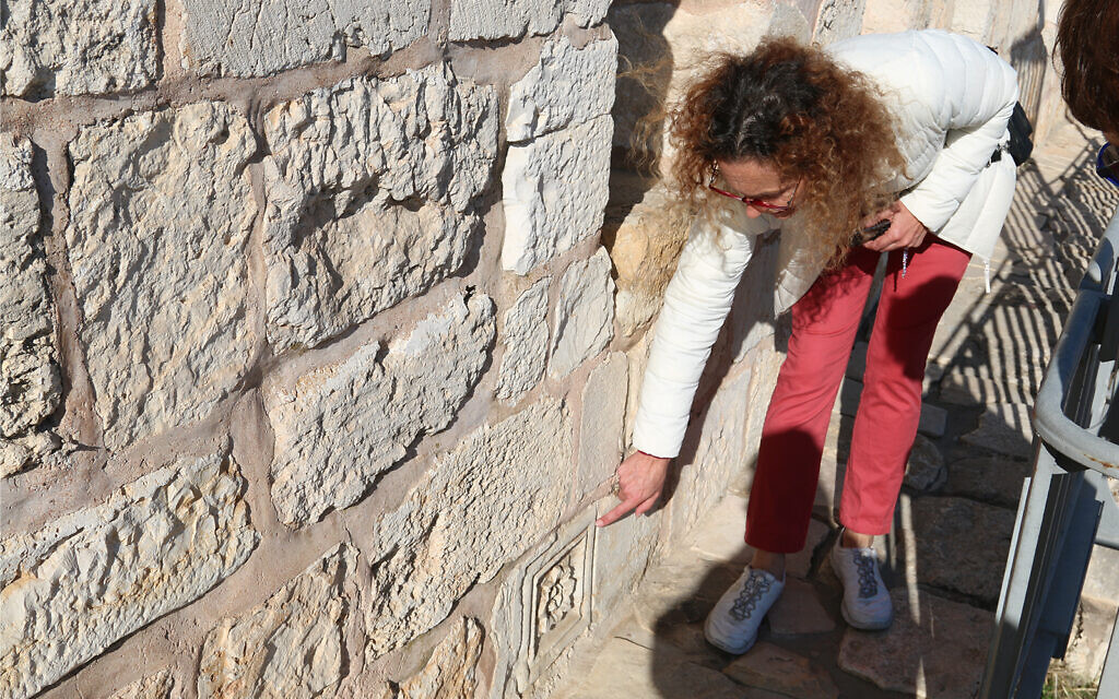 A tour guide points out ancient decorations carved into the ramparts wall of the Old City. (Shmuel Bar-Am)
