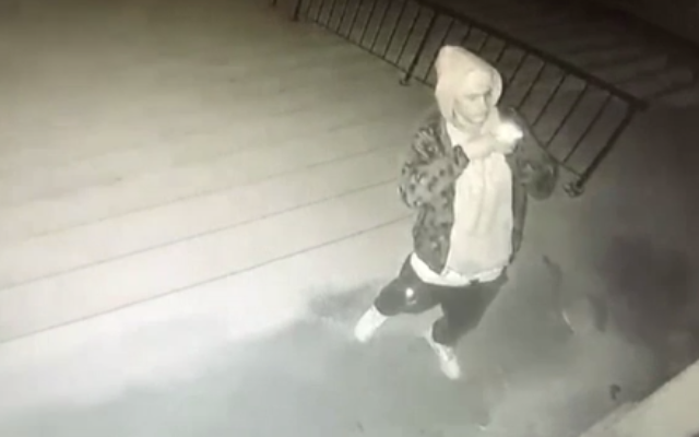 Security cam footage shows man taking photo after spraying swastika and racial epithets on stairs and door of a synagogue in Lincoln, Nebraska (video screenshot)