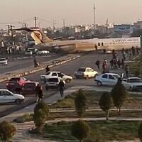 Scene after an Iranian passenger airliner carrying some 150 passengers skidded off the runway and into a street next to the airport in the southern city of Mahshahr, January 27, 2020 (Screen capture: Twitter)