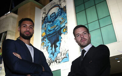 Chelsea soccer players Cesar Azpilicueta, right, and Ruben Loftus-Cheek stand against the club's mural commemorating Holocaust victims in London, Jan. 15, 2020.(Courtesy of Chelsea FC via JTA)