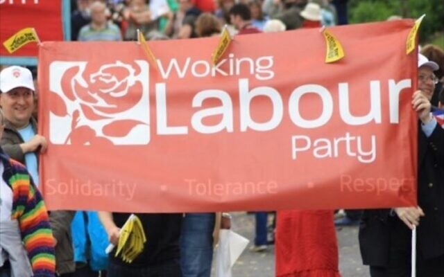People hold a sign reading, 'Woking the Labour Party.' (via AJC)