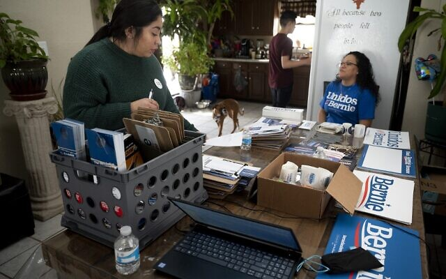 Latinx, a Latin American community outreach organization, and Democratic presidential candidate Bernie Sanders organizer Candy Alfaro (L) readies canvassing equipment with Spanish Satellite Captain Rosa Salazar (R) in Muscatine, Iowa on February 1, 2020. (Jim Watson/AFP)
