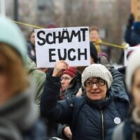 One day after the election of Thuringia's State Premier, a woman holds a placard reading 'Shame on you' during a protest in front of the State Chancellery in Erfurt, eastern Germany, on February 6, 2020 (Jens Schlueter / AFP)