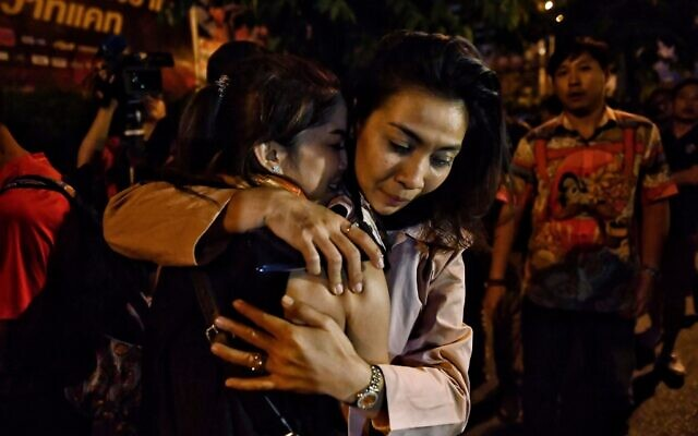 People hug each other after being rescued by Thai commandos from the Terminal 21 shopping mall, where a mass shooting took place on February 9, 2020 in the northeastern Thai city of Nakhon Ratchasima. (Lillian SUWANRUMPHA/AFP)