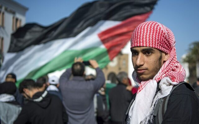 A Moroccan man walks next to a Palestinian flag during a demonstration against the US Middle East peace plan in the capital Rabat on February 9, 2020. (FADEL SENNA / AFP)