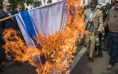 Illustrative: Moroccans burn the Israeli flag during a demonstration against the US Middle East peace plan in the capital Rabat on February 9, 2020. (FADEL SENNA / AFP)
