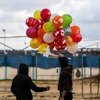 Masked Palestinians prepare to release an incendiary device near Gaza's Bureij refugee camp, along the Israel-Gaza border fence, on February 10, 2020 (MAHMUD HAMS / AFP)