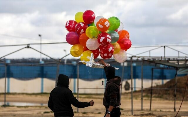 Masked Palestinians prepare to release an incendiary device near Gaza's Bureij refugee camp, along the Israel-Gaza border fence, on February 10, 2020 (MAHMUD HAMS / AFP)