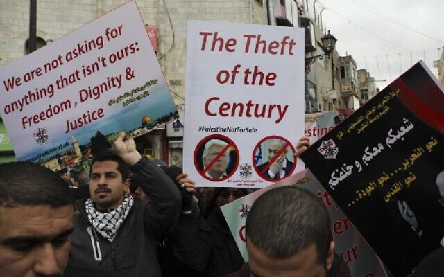 Palestinian protesters hold up placards as they demonstrate against a US-brokered peace proposal in the West Bank city of Ramallah, on February 11, 2020 (ABBAS MOMANI / AFP)