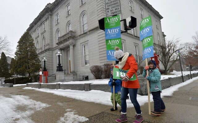 Supporters of Democratic presidential candidate Sen. Amy Klobuchar of Minnesota walk by the State House during the New Hampshire primary in Concord, New Hampshire on February 11, 2020. (Joseph Prezioso/AFP)