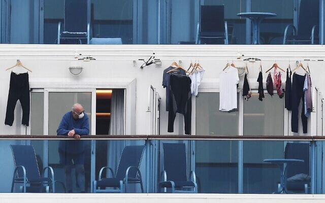 A passenger is seen on a balcony of the Diamond Princess cruise ship, with around 3,600 people quarantined onboard due to fears of the new coronavirus, at the Daikoku Pier Cruise Terminal in Yokohama port on February 14, 2020. (CHARLY TRIBALLEAU / AFP)