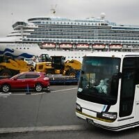 A bus with a driver wearing full protective gear departs from the dockside next to the Diamond Princess cruise ship, at the Daikoku Pier Cruise Terminal in Yokohama port on February 14, 2020 (CHARLY TRIBALLEAU / AFP)