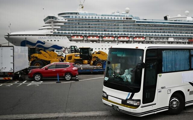 A bus with a driver wearing full protective gear departs from the dockside next to the Diamond Princess cruise ship, at the Daikoku Pier Cruise Terminal in Yokohama port on February 14, 2020. (CHARLY TRIBALLEAU / AFP)