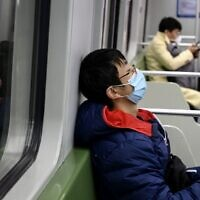 A subway passenger wearing a protective facemask sleeps on a train in Shanghai on February 14, 2020 (NOEL CELIS / AFP)