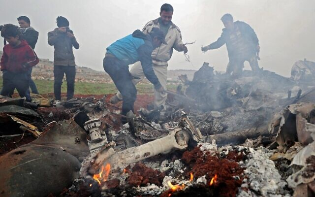People search for scraps of metal among the debris of a Syrian military helicopter that was shot down on February 14, 2020, in the western countryside of Aleppo province. (Omar Haj Kadour/AFP)