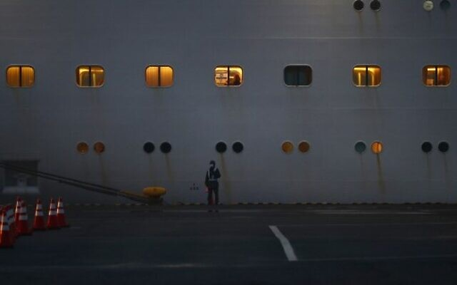 An officer stands next to the Diamond Princess cruise ship on February 16, 2020, with an Israeli flag visible through a window of the ship. (Behrouz MEHRI / AFP)