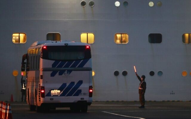 An Israeli flag can be seen in one of the portholes (left) of Diamond Princess cruise ship, where three Israelis have been diagnosed with coronavirus, at the Daikaku Pier Cruise Terminal in Yokohama port on February 16, 2020 (Behrouz MEHRI / AFP)