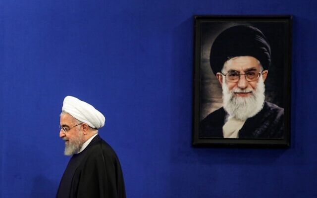 Iranian President Hassan Rouhani walks past a portrait of Supreme Leader Ayatollah Ali Khamenei as he arrives for a news conference in the capital Tehran, on February 16, 2020.(Photo by ATTA KENARE / AFP)