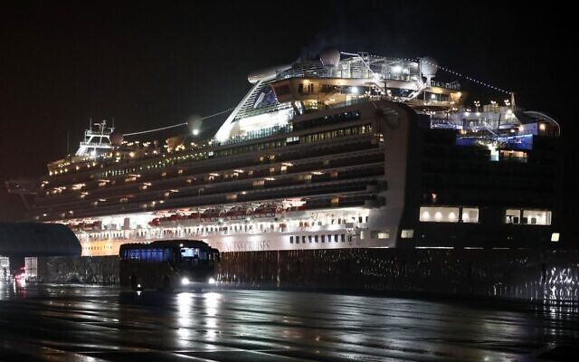 A bus carrying US citizens leaves the Daikaku Pier Cruise Terminal in Yokohama port, next to the Diamond Princess cruise ship, with people quarantined on board due to fears of the new COVID-19 coronavirus, February 17, 2020. (Behrouz Mehri/AFP)