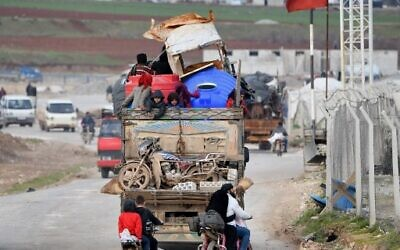 Vehicles carrying internally-displaced persons (IDPs) and their belongings drive past the IDP camp by Dayr Ballut near the Turkish border in the west of the northern Syrian province of Aleppo on February 16, 2020, as people flee advancing government forces in Idlib and Aleppo provinces. (Rami al SAYED / AFP)