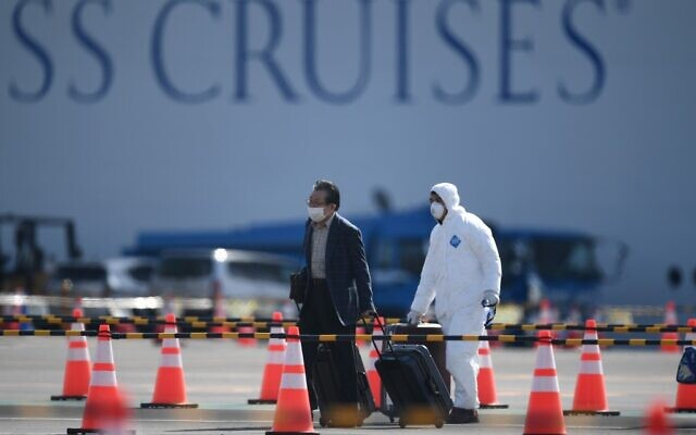 A passenger (L) disembarks from the Diamond Princess cruise ship - in quarantine due to fears of the new COVID-19 coronavirus - at the Daikoku Pier Cruise Terminal in Yokohama on February 19, 2020. (Photo by CHARLY TRIBALLEAU / AFP)