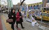 Iranian women walk past electoral posters and fliers during the last day of election campaign in Tehran on February 19, 2020. (ATTA KENARE / AFP)