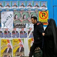 Iranians walk past electoral posters and fliers during the last day of election campaign in Tehran on February 19, 2020 (ATTA KENARE / AFP)