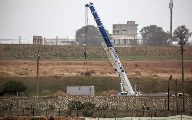 A picture taken in Rafah in the southern Gaza Strip at the border with Egypt shows a crane at the construction site of a wall on the Egyptian side of the border on February 19, 2020. (Said Khatib/AFP)