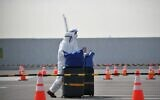 Workers in protective suits help passengers with their luggages from the Diamond Princess cruise ship, in quarantine due to fears of new COVID-19 coronavirus, at Daikoku pier cruise terminal in Yokohama on February 20, 2020. (Philip FONG / AFP)