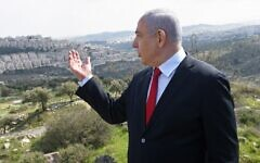 Prime Minister Benjamin Netanyahu stands at an overview of the East Jerusalem neighborhood of Har Homa on February 20, 2020. (Debbie Hill/Pool/AFP)