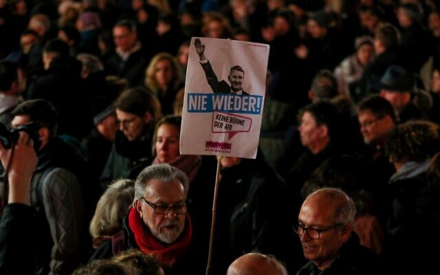 A man holds a placard featuring Regional leader of AfD Thuringia Bjoern Hoecke and the words 'Never again' during a vigil in Hanau, near Frankfurt am Main, western Germany, on February 20, 2020, after at least nine people were killed in two shootings late on February 19, 2020 (Odd ANDERSEN / AFP)
