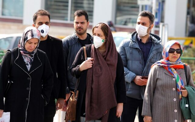Iranians, some wearing protective masks, wait to cross a street in the capital Tehran on February 22, 2020. (ATTA KENARE / AFP)