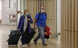 Passengers wearing protective masks walk at the arrival hall of Ben Gurion International Airport on February 22, 2020.  (Ahmad GHARABLI/AFP)