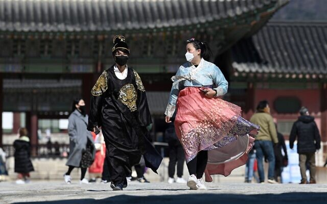 People in traditional Korean hanbok dresses wear face masks as they visit Gyeongbokgung palace in Seoul on February 23, 2020 (Jung Yeon-je / AFP)