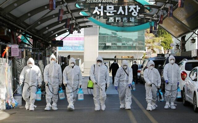 Market workers wearing protective gear spray disinfectant at a market in the southeastern city of Daegu, South Korea, on February 23, 2020, as a preventive measure after the COVID-19 coronavirus outbreak. (YONHAP / AFP)