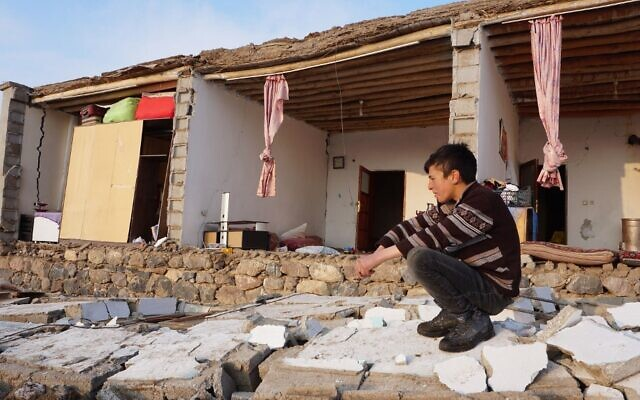 A Turkish child kneels by a destroyed house in Baskale, in the Van province, after a magnitude 5.7 earthquake in northwestern Iran killed at least nine people in neighboring Turkey and injured dozens more on both sides of the border, authorities said, on February 23, 2020. (Demiroren News Agency (DHA)/AFP)