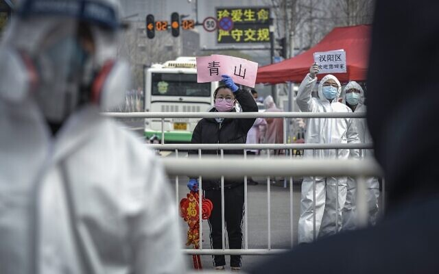 This photo taken on February 22, 2020 shows a woman welcoming people who have recovered from the COVID-19 coronavirus infection as they are discharged from the hospital in Wuhan in China's central Hubei province. (Photo by STR / AFP)
