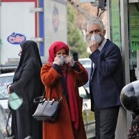 People wearing protective masks wait along the side of a street in the Iranian capital Tehran on February 24, 2020 (Atta Kenare/AFP)