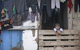 A Palestinian boy looks out from within a shop in the Khan Younis refugee camp in the southern Gaza Strip, on February 24, 2020. (MOHAMMED ABED / AFP)