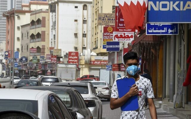 A man wearing a surgical mask is pictured in the heart of the Bahraini capital Manama on February 26, 2020. (Mazen Mahdi/AFP)