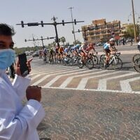 A man wearing a surgical masks looks on as the pack rides by during stage five the UAE Cycling Tour from al-Maroom to Jebel Hafeet, in Dubai on February 27, 2020. (Giuseppe CACACE / AFP)