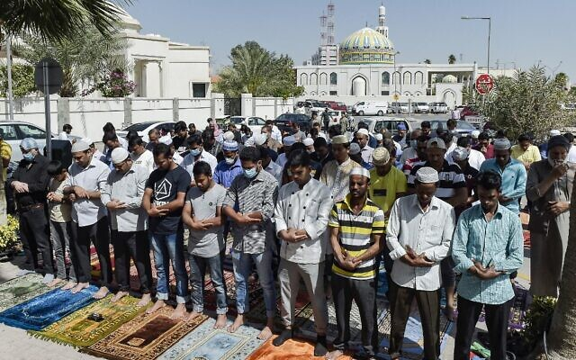 Muslim worshippers, some wearing protective masks, perform together Friday prayers outside a mosque in Bahrain's capital Manama on February 28, 2020. (Mazen Mahdi/AFP)