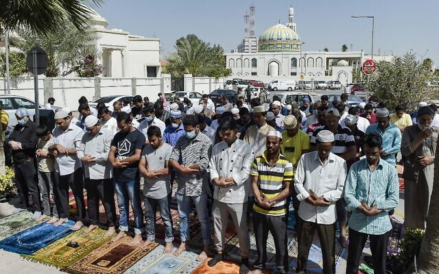 Muslim worshippers, some wearing protective masks, perform together Friday prayers outside a mosque in Bahrain's capital Manama on February 28, 2020 (Mazen Mahdi / AFP)
