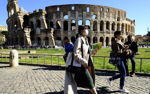 Tourists wearing a protective respiratory mask tour outside the Colosseum monument in downtown Rome on February 28, 2020 amid fear of Covid-19 epidemic (Andreas SOLARO / AFP)