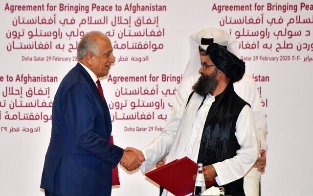 US Special Representative for Afghanistan Reconciliation Zalmay Khalilzad, left, and Taliban co-founder Mullah Abdul Ghani Baradar shake hands after signing a peace agreement during a ceremony in the Qatari capital Doha on February 29, 2020. (Giuseppe Cacace/AFP)