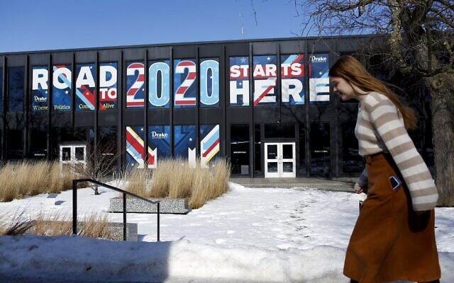 """A woman walks past a sign displayed on a building at Drake University that reads """"Road To 2020 Starts Here"""" on February 2, 2020 in Des Moines, Iowa. (Joshua Lott/Getty Images/AFP)"""