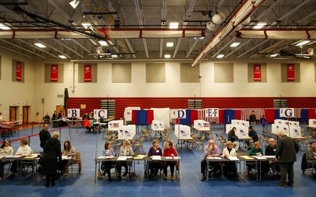 Poll workers wait for voters to check in at Bedford High School during the New Hampshire primary on February 11, 2020 in Bedford, New Hampshire. (Matthew Cavanaugh/Getty Images/AFP)