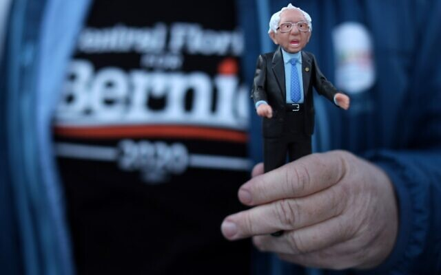 A supporter holds a Bernie Sanders action figure outside a campaign event for Democratic presidential candidate Sen. Bernie Sanders (Vermont independent) at Ingersoll Tap in Des Moines, Iowa on February 2, 2020. (Alex Wong/Getty Images/AFP)