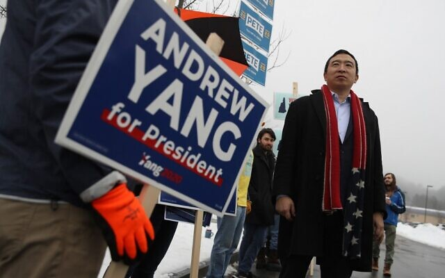 Democratic presidential candidate Andrew Yang greets supporters holding signs in front of a polling station on February 11, 2020 in Keene, New Hampshire. (Justin Sullivan/Getty Images/AFP)
